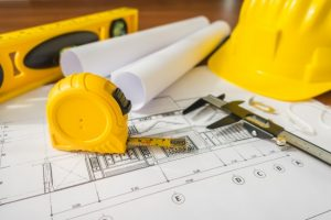 construction-plans-with-yellow-helmet-and-drawing-tools-on-bluep_1232-2940